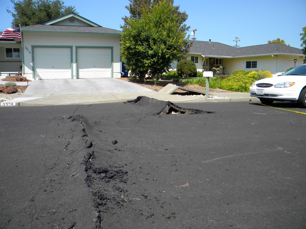 Fault damage in the suburbs west of Napa, California from the August 24th magnitude 6 earthquake. The fault rupture ran through homes and across roads, buckling the tarmac surface and pavements, resulting in damage expected to cost hundreds of millions of dollars. Photo credit: Austin Elliott, UC Davis.