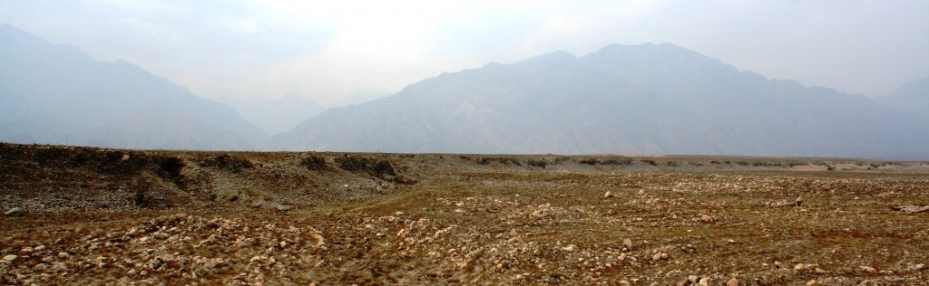 Figure 1: Field photograph of the Suyukou fault scarp. The scarp is around 8 metres high and can be seen cutting across the centre of the picture. In the distance, a few kilometres away to the west, are the Helan Mountains.